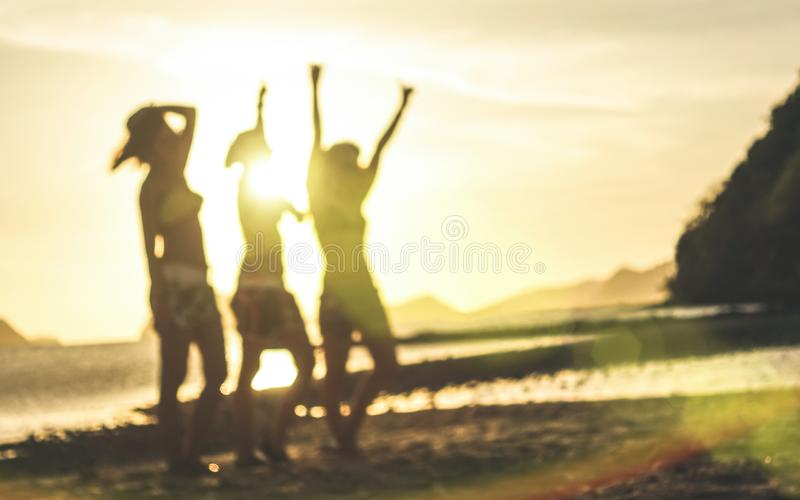 Blurred defocused silhouette of women travelers at sunset - Travel wanderlust concept with young girlfriends partying and dancing stock image