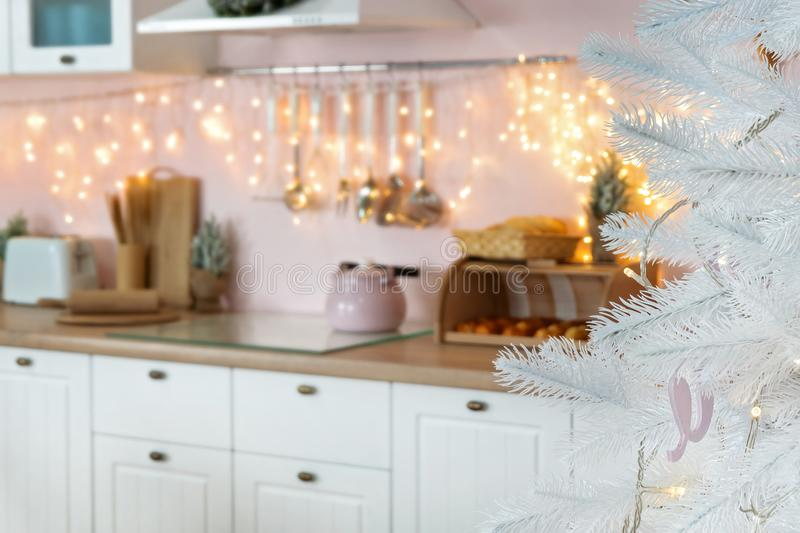 Blurred defocused view on interior of modern white kitchen with pink walls and blue decor on a Christmas New year eve. Pine tree royalty free stock photo