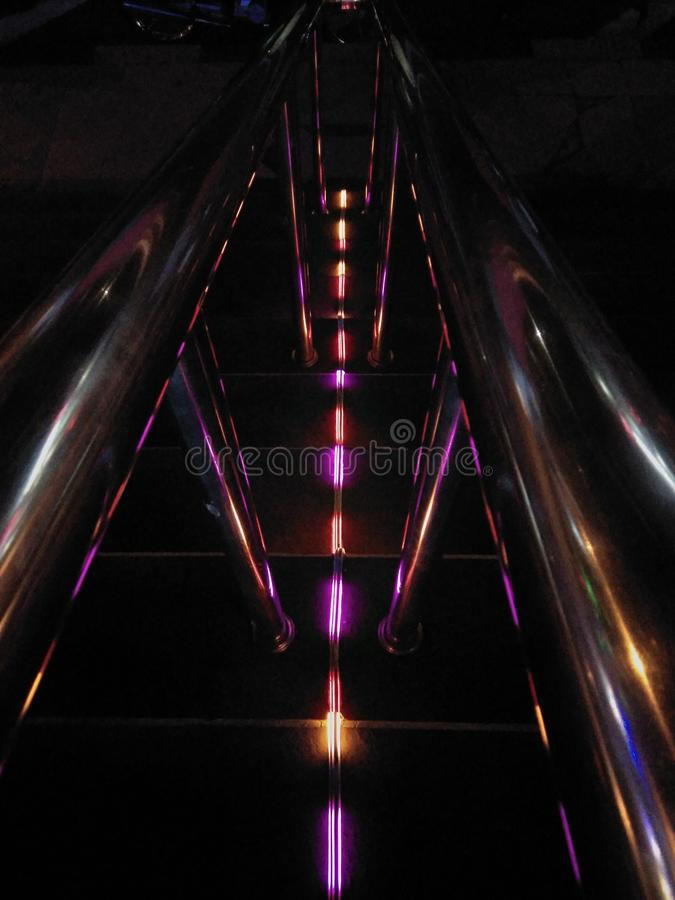 Blurred and Defocussed lights form a digital neon color matrix. on the stairs. Blues, pink, aqua and white stock illustration