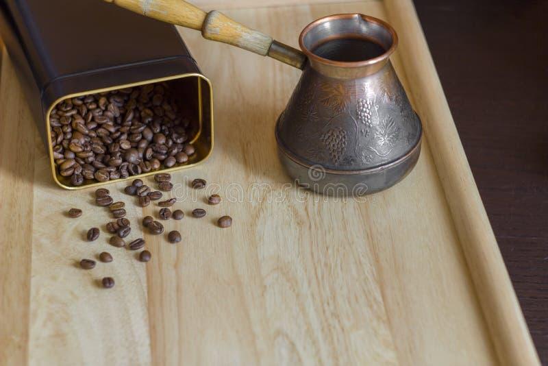 Blurred dispersó los granos de café asados marrones de una poder en la superficie ligera de la tabla y de un fabricante de café d foto de archivo libre de regalías