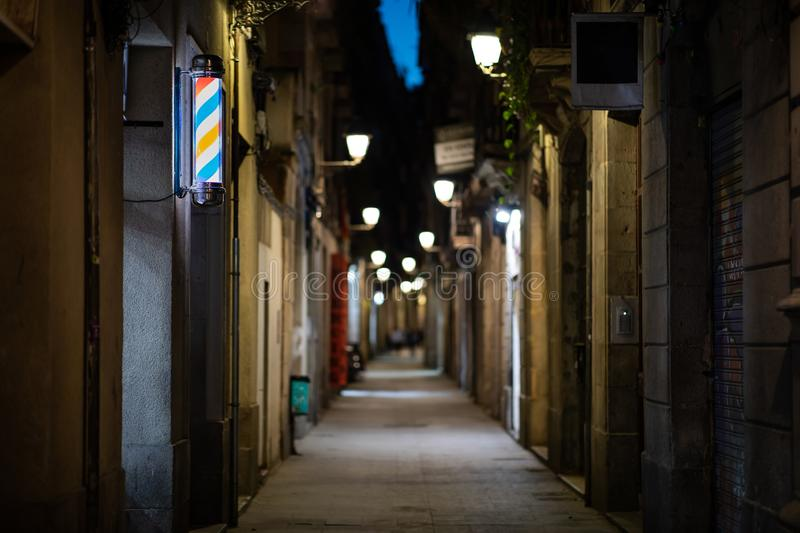 Blurred downtown alley at night with barbershop or hairdresser& x27;s sign on the wall. With copy space, road, residential, shadow, black, street, stone, brick royalty free stock photo