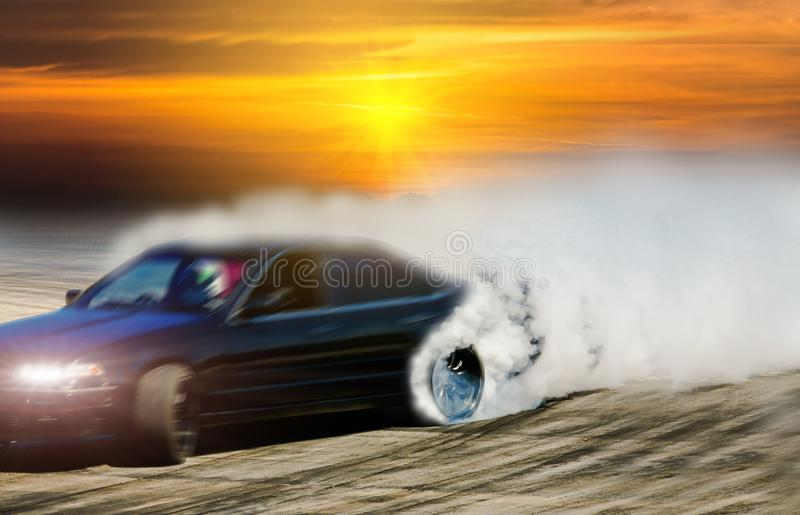 Blurred drift car on race track with smoke from burned tire. At sunset royalty free stock images