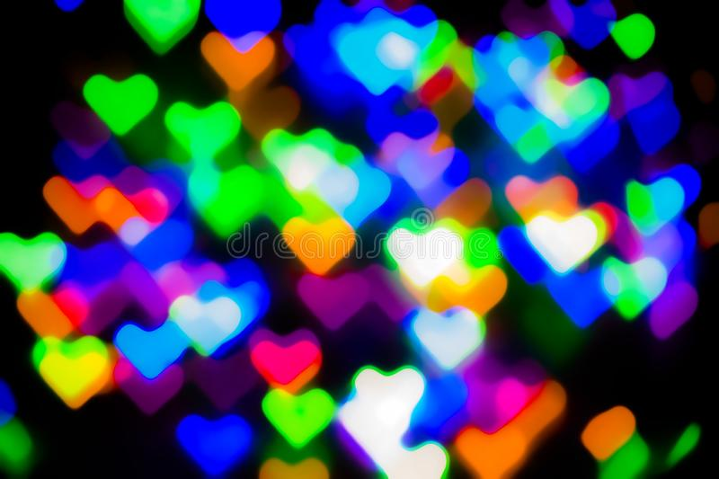 Blurred festive background with defocused colourful glitter formed a heart, bokeh in a shape of a heart. Original photographic. Effect. Pictures concept theme stock photos