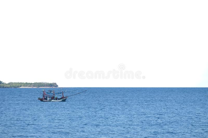 Blurred a fishing boat sailing in a deep blue sea with white sky background stock photography
