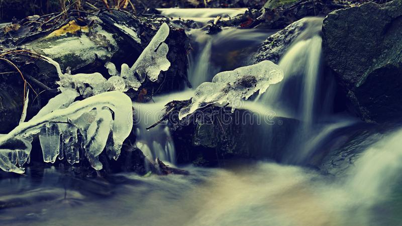 Blurred flowing water in winter creek. Beautiful photo of winter nature in the forest royalty free stock image