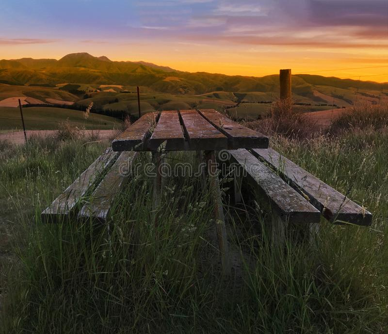 Blurred Focused Beautiful twilight picturesque farmland view of Middle Valley, Canterbury, New Zealand. Wooden bench and table in royalty free stock photos