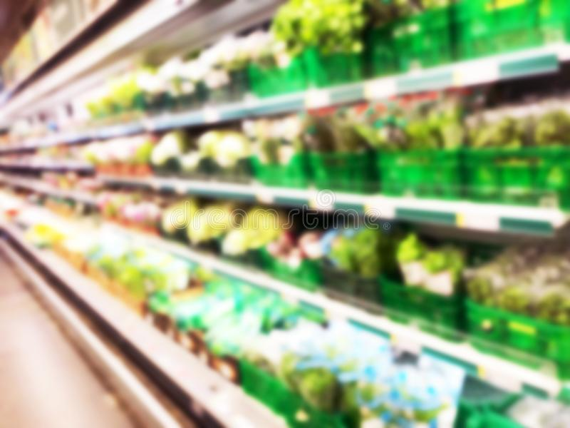 Blurred fresh fruits and vegetables at retail store. Abstract background of supermarket. Grocery market blurred background. Fruits. In store racks. Interior royalty free stock image