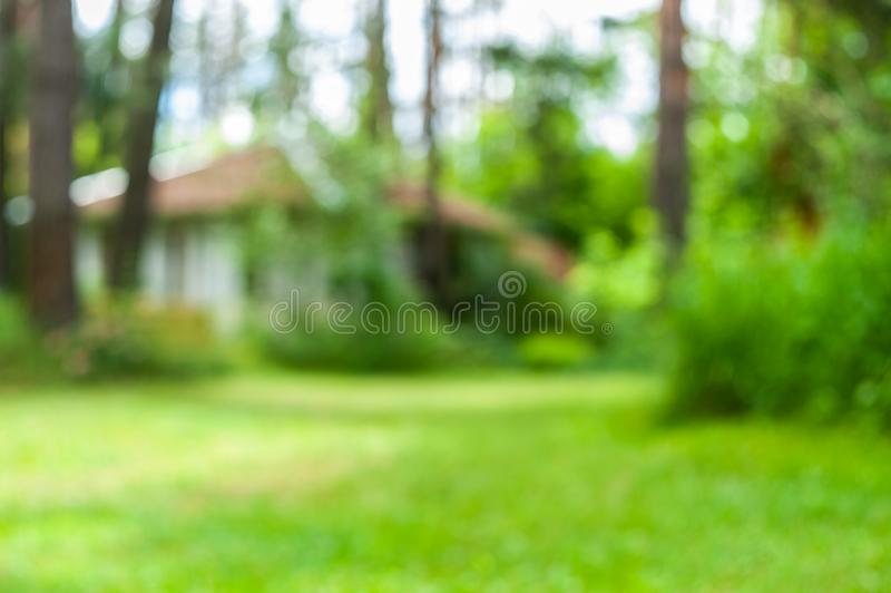 Blurred garden background with forest trees, grass and white alcove. On the back royalty free stock image