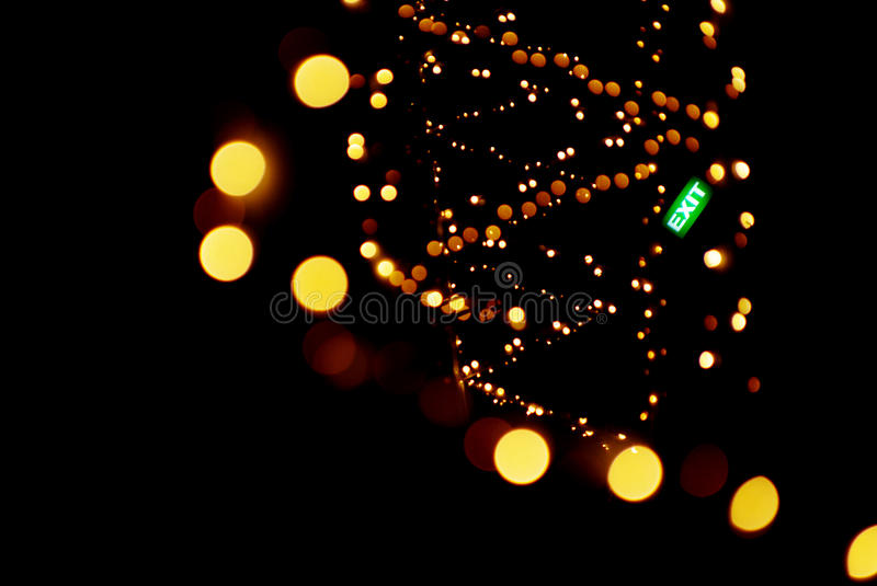 Blurred garland lights whirl. Background: blurred garland lights in whirl with exit sign in focus isolated on black royalty free stock photography