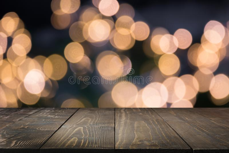Blurred gold garland and wooden tabletop as foreground. Image for display your christmas products royalty free stock images