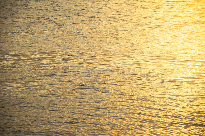 blurred of Golden rippled water surface an the sunrise stock image