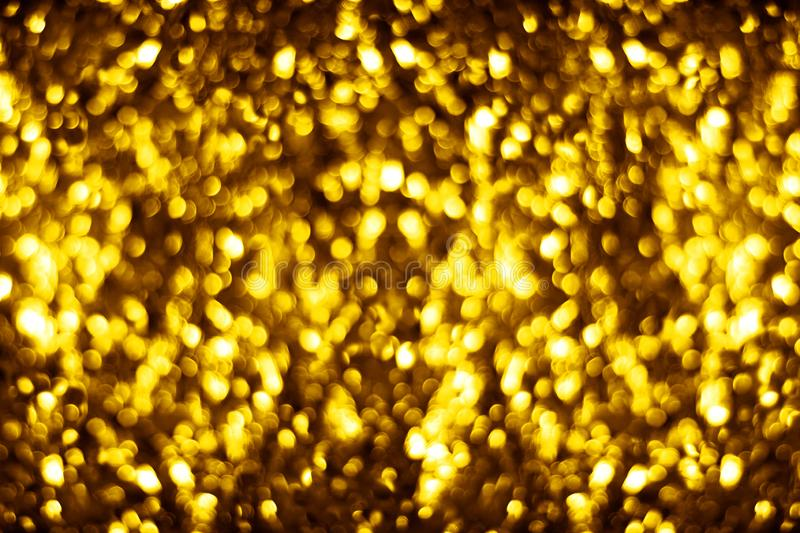 Blurred golden shiny glitter bokeh background, defocused yellow shimmer backdrop design, gold shining round bubbles blur effect royalty free stock photo
