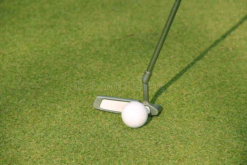 Blurred golf club and golf ball close up in grass field stock image