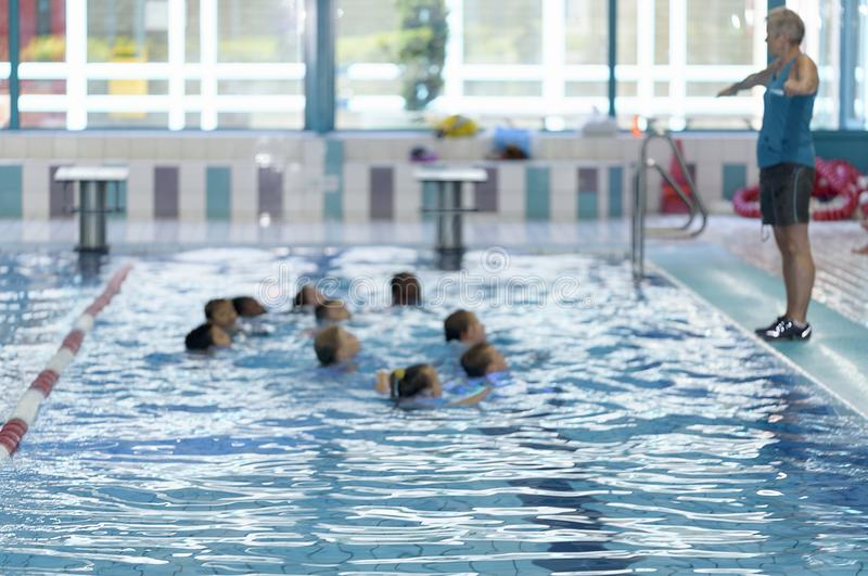 Blurred. Group of Children learn to swim in the pool stock photos