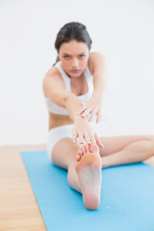 Blurred ha tonificato la donna che fa l'allungamento del tendine del ginocchio sulla stuoia di esercizio nello studio di forma fis fotografia stock libera da diritti