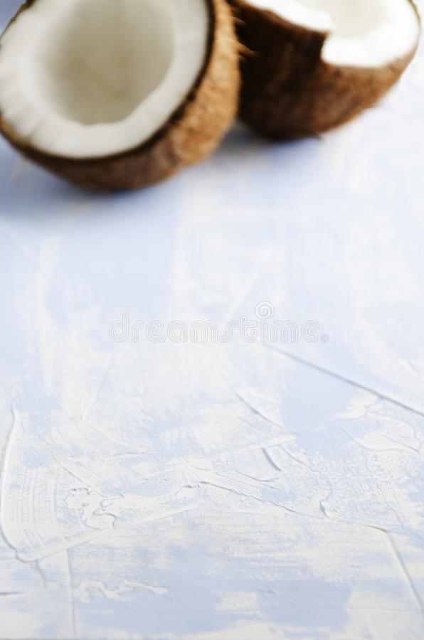 Blurred halfs of coconut in the bakground, blue surface, empty space for text royalty free stock photo