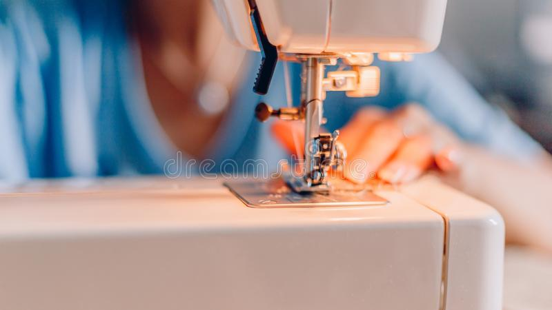 Blurred Hands of sewing process. Female hands stitching fabric on machine. royalty free stock photo