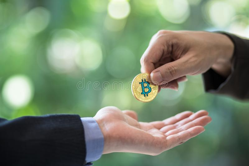 Blurred Hands of two businessmen are trading coin of bitcoin. A symbolic coins of bitcoin. electronic money exchange royalty free stock photography