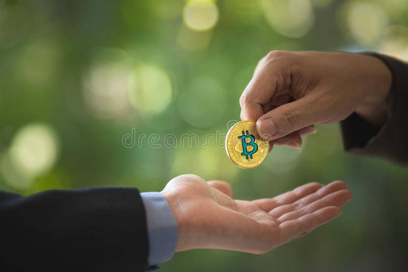 Blurred Hands of two businessmen are trading coin of bitcoin. A symbolic coins of bitcoin. stock images