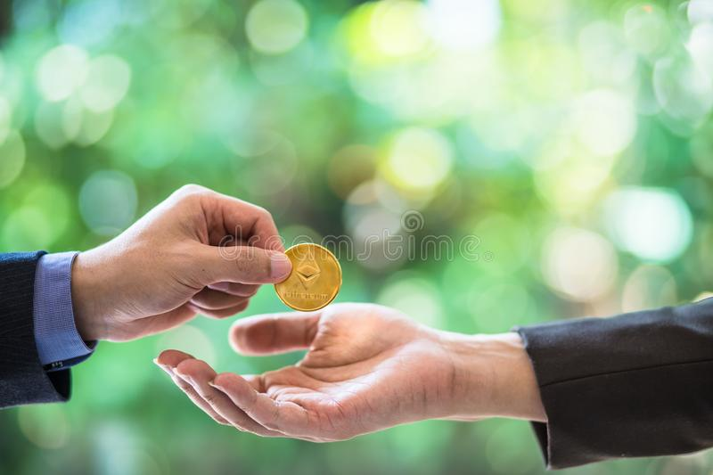 Blurred Hands of two businessmen are trading coin of ethereum. A symbolic coins of ethereum. electronic money exchange, royalty free stock image