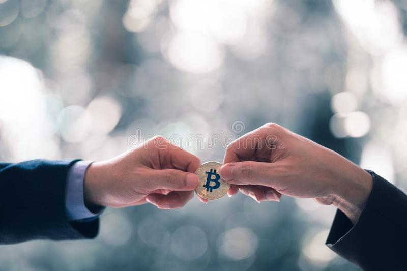 Blurred Hands of two businessmen are trading coin of ethereum. A symbolic coins of ethereum. stock photo