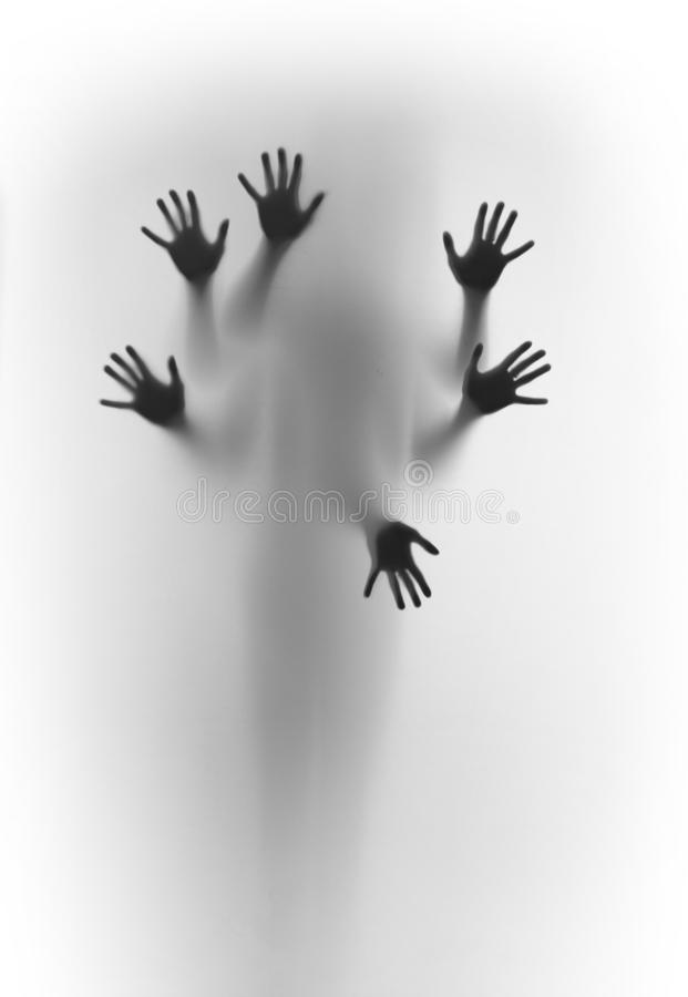 Blurred human body shape spirit stands behind diffuse surface, six hands can be seen sharply, fingers and palms. Hidden human body blurred silhouette, and six royalty free stock photo