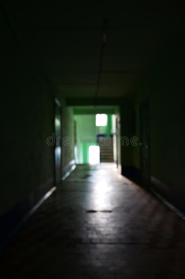 The blurred image of gloomy corridor of a neglected public building. Defocused picture of a public space in a poor residential hi. Gh-rise building stock photos