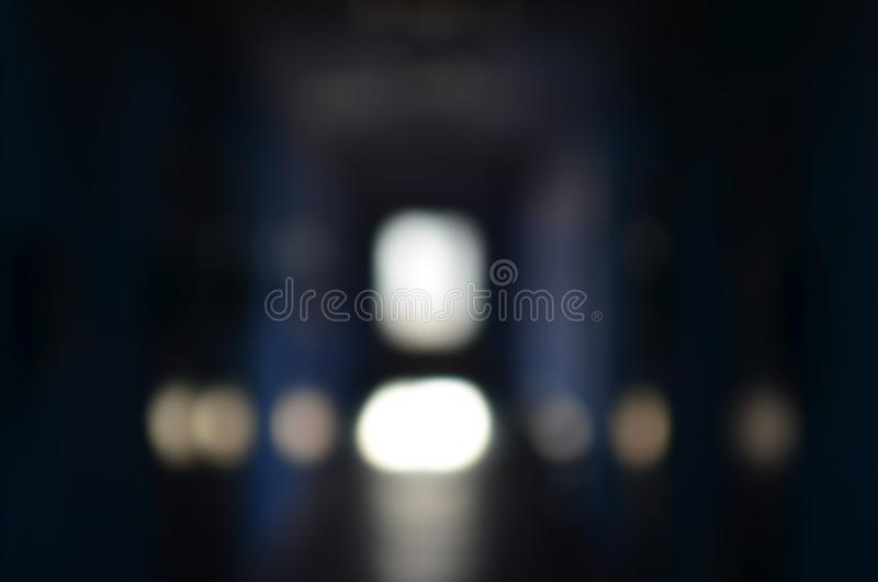 The blurred image of gloomy corridor of a neglected public building. Defocused picture of a public space in a poor residential hi. Gh-rise building stock photography