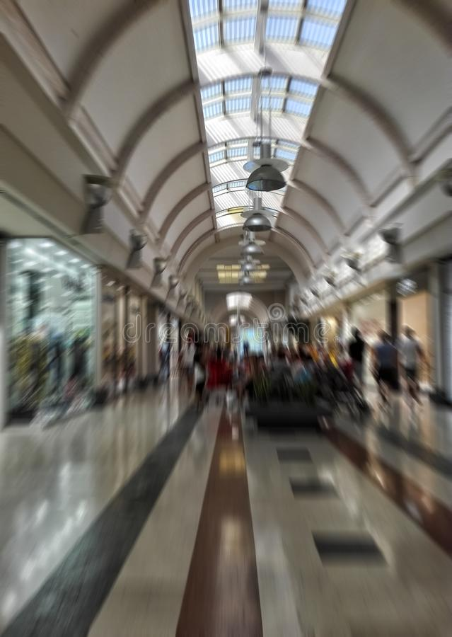 Blurred image of indoor mall gallery with fashion stores on both sides. stock photos