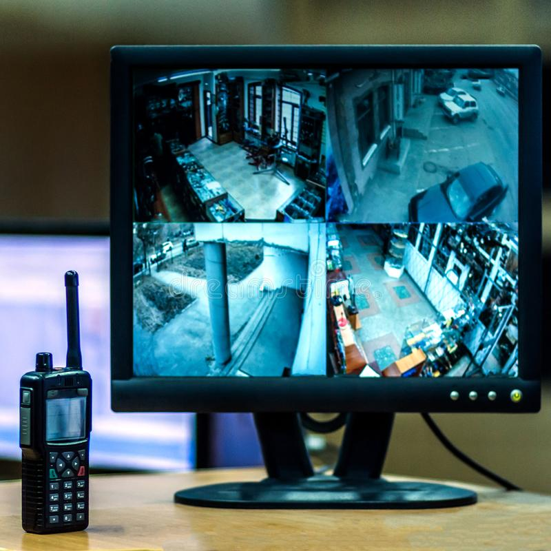 Blurred image on the monitor screen from four cameras by video surveillance. Workplace. CCTV. The policeman`s radio is nearby. Sq royalty free stock image