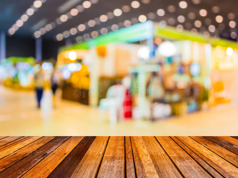 Blurred image of people at trade show. Blurred image of wood table and trade show in shopping mall for background usage stock images