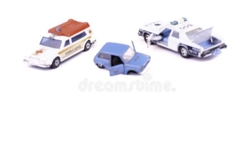 Blurred image smashed up and broken from accident or malfunction childrens toy car isolated on white background with ambulance and. Police on crash site helping stock photo