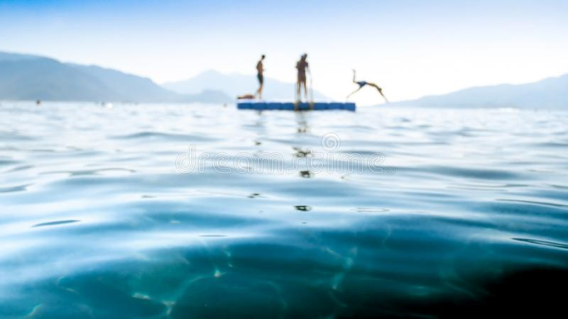 Blurred image of young men jumping from floating pontoon in the sea. Blurred photo of young men jumping from floating pontoon in the sea stock images