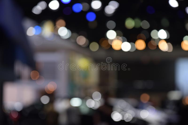 Bokeh of light in the car showroom at the motor show. Blurred images and beautiful bokeh of light in the car showroom at the motor show royalty free stock photos