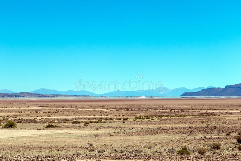 Blurred landscape of Bolivian desert in sunny day with blue sky Eduardo Avaroa Park, Bolivia. Blurred bright landscape of roadside in desert of the Eduardo stock photography