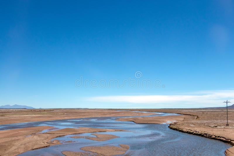 Blurred landscape of Bolivian desert in sunny day with blue sky Eduardo Avaroa Park, Bolivia. Blurred bright landscape of roadside in desert of the Eduardo royalty free stock image