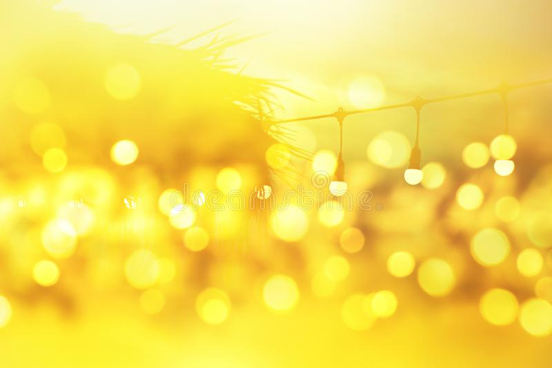 Blurred light bokeh on sunset, yellow string lights in outdoor restaurant, abstract background stock photography