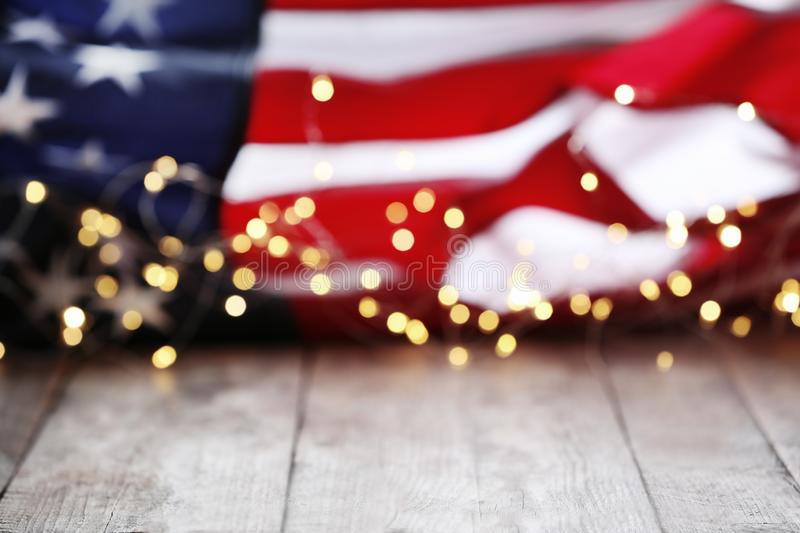 Blurred lights and American flag on wooden table. Mockup for design royalty free stock image