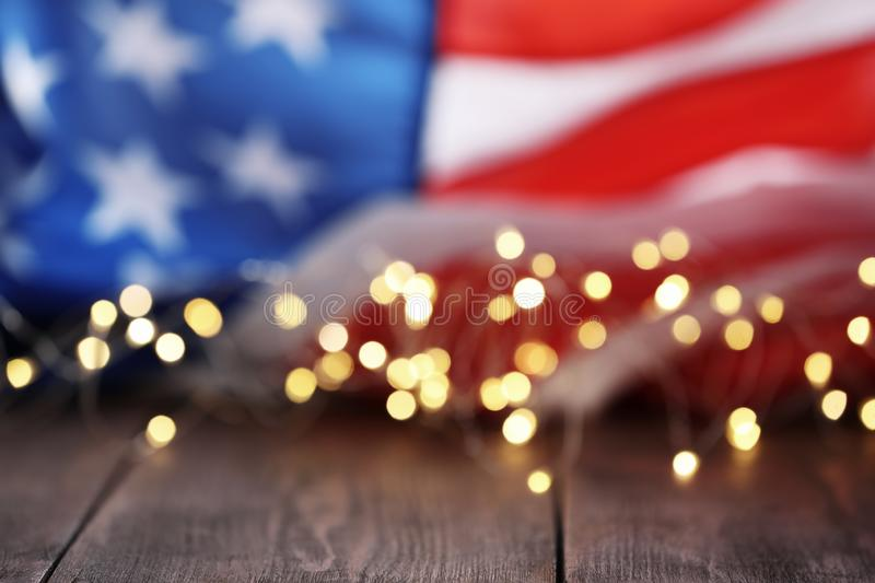 Blurred lights and American flag on wooden table. Mockup for design stock images