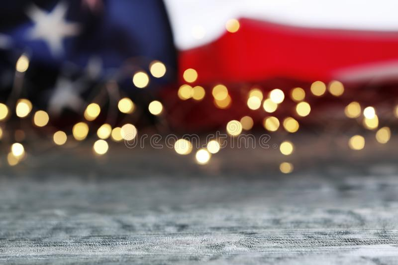 Blurred lights and American flag on wooden table. Mockup for design stock image