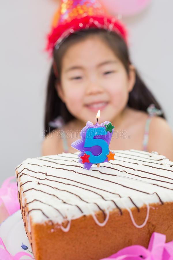 Blurred little girl with lit candle on birthday cake stock photo