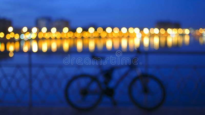 Blurred a modifié la tonalité le fond avec les lumières brouillées de ville avec la réflexion en silhouette de rivière et de vélo photo stock