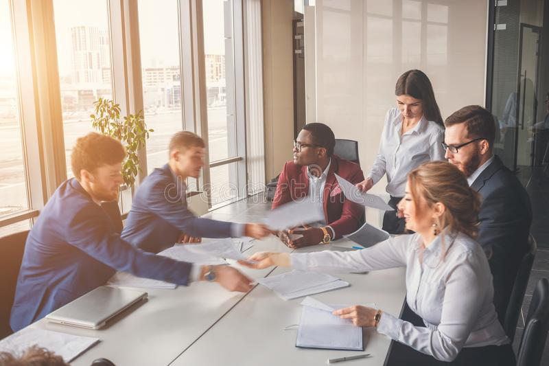 Blurred motion businesspeople working with boss sitting in background at office stock image