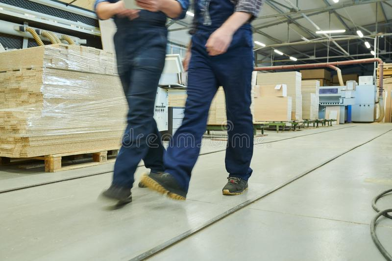 Blurred motion of factory men in overalls royalty free stock photo