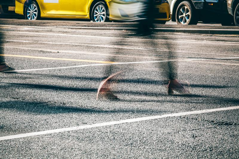 Blurred motion of person legs crossing busy street. stock photo