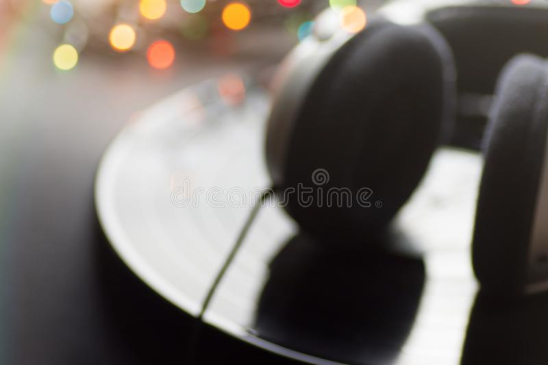 Blurred Music Background. Headphones Lying on Vintage Vinyl Long Play Record Black Background Multicolored Bokeh Lights stock photos