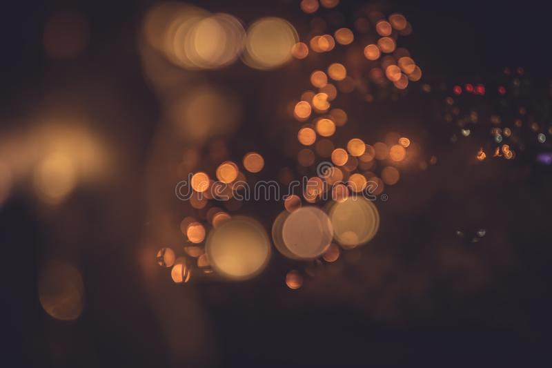 Blurred night city lights in warm colors through window reflection of street lights in retro style. Blurred night city lights in warm colors through window stock images