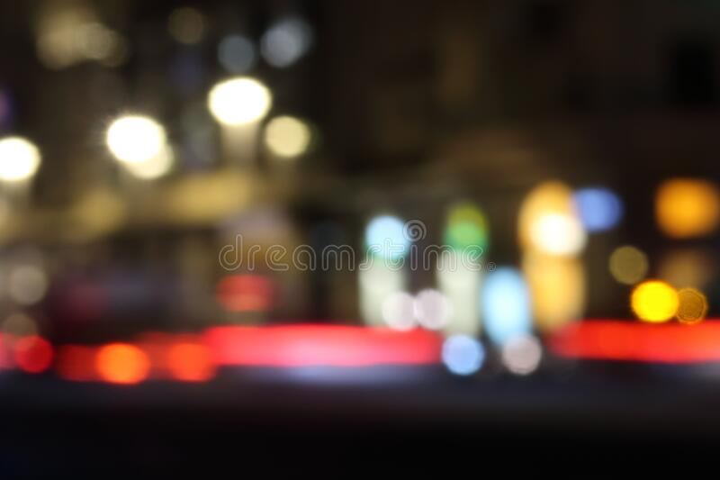 Blurred night city and traffic lights. Background with bright color spots and bokeh on black.  royalty free stock image