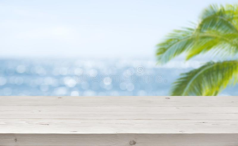 Blurred ocean background with wooden table foreground for product display stock images