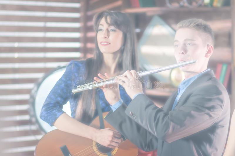 Blurred overexposed photo for background use. A guy in a suit with a flute, a girl in a blue dress with a guitar. Retro style. stock photos